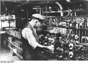 Pictured above is a Belgian worker who was forcibly taken from his home and made to work as a winder (someone who operates the bobbin) at the Siemens factory in Berlin, where enameled wires were manufactured. This photo, from August of 1943, was taken by order of Siemens and thus cannot be considered representative of actual working conditions in the factory. Source: Bundesarchiv, Bild 183-R46093 / CC-BY-SA, http://en.wikipedia.org/wiki/File:Bundesarchiv_Bild_183-R46093,_Belgischer_Zwangsarbeiter_bei_Siemens.jpg